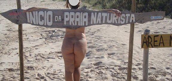 Esposa nua na praia de nudismo