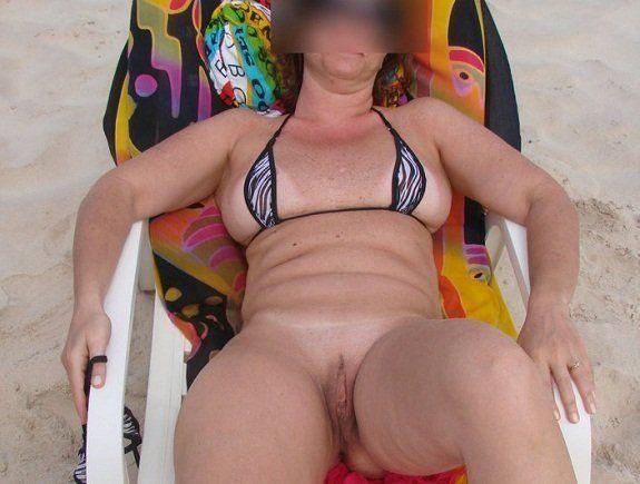 Mulher de corno na praia de biquíni